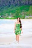 Muchacha adolescente hermosa en vestido verde que camina a lo largo de la playa hawaiana Fotografía de archivo libre de regalías