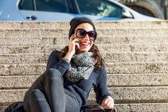 Muchacha adolescente hermosa inclinada detrás y hablando en el teléfono Fotografía de archivo
