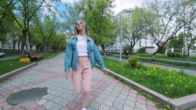 Muchacha adolescente hermosa que escucha la música que camina a lo largo de las calles viejas de la ciudad y de la mujer feliz de almacen de metraje de vídeo