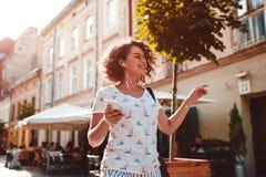 Muchacha adolescente hermosa que escucha la música que camina a lo largo de las calles viejas y del baile de la ciudad Imagen de archivo
