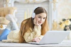 Muchacha adolescente hermosa que miente en piso y que usa el ordenador portátil Imagen de archivo