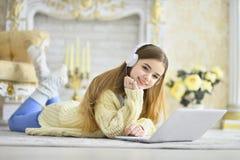 Muchacha adolescente hermosa que miente en piso y que usa el ordenador portátil Fotos de archivo