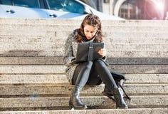 Muchacha adolescente hermosa que mira la tableta Imagen de archivo