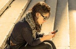 Muchacha adolescente hermosa que mira su smartphone - filtro caliente Foto de archivo libre de regalías