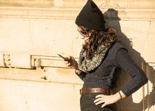 Muchacha adolescente hermosa que mira su smartphone - filtro caliente Fotos de archivo