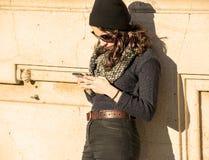 Muchacha adolescente hermosa que mira su smartphone - filtro caliente Imágenes de archivo libres de regalías