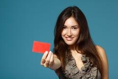 Muchacha adolescente hermosa que muestra la tarjeta roja a disposición, sobre azul Imagenes de archivo