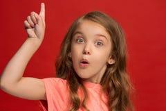 Muchacha adolescente hermosa que parece sorprendida aislado en rojo Foto de archivo libre de regalías