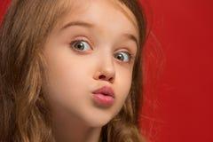 Muchacha adolescente hermosa que parece sorprendida aislado en rojo Fotos de archivo libres de regalías