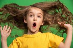 Muchacha adolescente hermosa que parece sorprendida aislado en verde Fotos de archivo libres de regalías