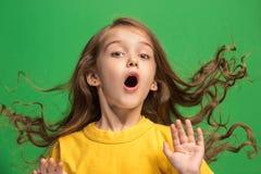 Muchacha adolescente hermosa que parece sorprendida aislado en verde Fotos de archivo