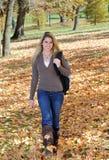 Muchacha adolescente hermosa que recorre en hojas de otoño Fotografía de archivo libre de regalías