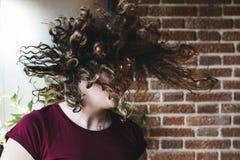 Muchacha adolescente hermosa que sacude la cabeza con el pelo rizado Imagenes de archivo