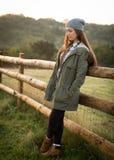Muchacha adolescente hermosa que se inclina contra una cerca de la granja Imagen de archivo
