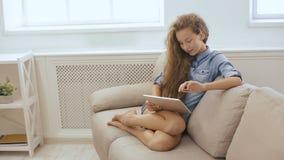 Muchacha adolescente hermosa que se relaja en el sofá con la tableta Tiro de Steadicam de una muchacha linda que se relaja en el  metrajes