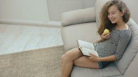 Muchacha adolescente hermosa que se relaja en el sofá que lee un libro y que come la manzana almacen de metraje de vídeo