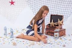 Muchacha adolescente hermosa que se sienta en el infante de marina del piso Fotos de archivo libres de regalías