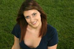 Muchacha adolescente hermosa que se sienta en hierba Imagen de archivo
