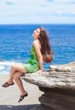 Muchacha adolescente hermosa que se sienta en la repisa rocosa sobre el océano azul Foto de archivo libre de regalías