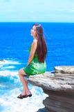 Muchacha adolescente hermosa que se sienta en la repisa rocosa sobre el océano azul Fotos de archivo libres de regalías