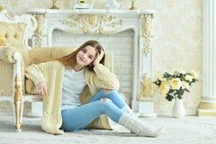 Muchacha adolescente hermosa que se sienta en piso cerca de la butaca del vintage Foto de archivo