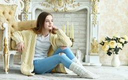 Muchacha adolescente hermosa que se sienta en piso cerca de la butaca del vintage Fotos de archivo
