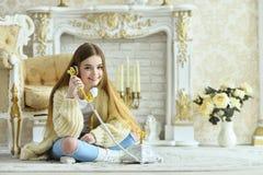 Muchacha adolescente hermosa que se sienta en piso y que habla en phon del vintage Fotos de archivo
