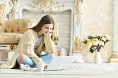 Muchacha adolescente hermosa que se sienta en piso y que usa el ordenador portátil Imagen de archivo