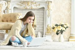 Muchacha adolescente hermosa que se sienta en piso y que usa el ordenador portátil Fotos de archivo libres de regalías