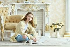 Muchacha adolescente hermosa que se sienta en piso y que usa el ordenador portátil Imagenes de archivo