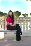 Muchacha adolescente hermosa que se sienta en un banco al aire libre (1 Foto de archivo
