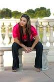Muchacha adolescente hermosa que se sienta en un banco al aire libre (2 Fotos de archivo libres de regalías