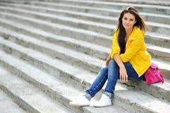 Muchacha adolescente hermosa que sienta en las escaleras en coágulo colorido Imagen de archivo libre de regalías