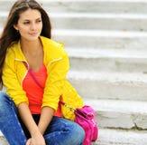Muchacha adolescente hermosa que sienta en las escaleras en coágulo colorido Fotografía de archivo libre de regalías