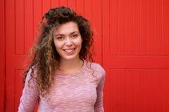 Muchacha adolescente hermosa que sonríe contra la pared roja Fotografía de archivo
