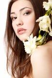 Muchacha adolescente hermosa que sonríe y con el narciso y el lookin de la flor Foto de archivo libre de regalías