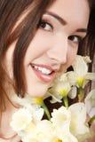 Muchacha adolescente hermosa que sonríe y con el narciso y el lookin de la flor Fotos de archivo libres de regalías