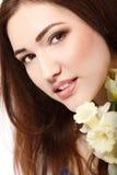 Muchacha adolescente hermosa que sonríe y con el narciso y el lookin de la flor Imagenes de archivo