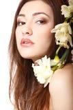Muchacha adolescente hermosa que sonríe y con el narciso y el lookin de la flor Imágenes de archivo libres de regalías