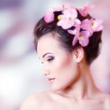 Muchacha adolescente hermosa que sonríe y con la orquídea de la flor Imagen de archivo libre de regalías
