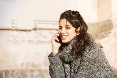 Muchacha adolescente hermosa que sonríe y que habla en el teléfono Foto de archivo libre de regalías