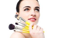 Muchacha adolescente hermosa que sostiene cepillos del maquillaje Fotos de archivo