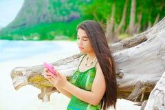 Muchacha adolescente hermosa que sostiene el teléfono móvil, en la playa hawaiana por dri Fotografía de archivo