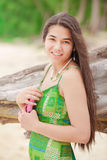 Muchacha adolescente hermosa que sostiene el teléfono móvil, sonriendo en beac hawaiano Imagenes de archivo