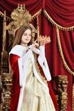 Muchacha adolescente hermosa que sostiene la corona mientras que se sienta en armch del vintage Imágenes de archivo libres de regalías