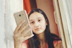 Muchacha adolescente hermosa que sostiene un teléfono móvil Estilo de la forma de vida fotos de archivo libres de regalías