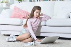 Muchacha adolescente hermosa que usa el ordenador portátil Foto de archivo libre de regalías