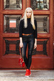 Muchacha adolescente hermosa rubia deportiva elegante joven en la presentación negra contra fondo rojo de la puerta del vintage E Foto de archivo