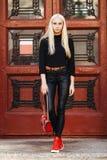 Muchacha adolescente hermosa rubia deportiva elegante joven en la presentación negra contra fondo rojo de la puerta del vintage E Fotografía de archivo