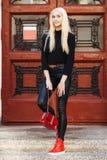 Muchacha adolescente hermosa rubia deportiva elegante joven en la presentación negra contra fondo rojo de la puerta del vintage E Imagenes de archivo